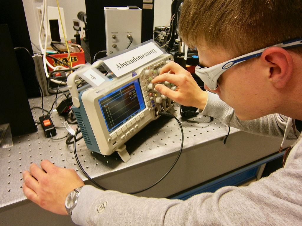 Hier bin ich an dem Gerät zu sehen, das mithilfe von einem Spiegel und einem Laser Abstandsmessungen ermöglicht.